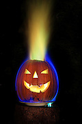 A carved pumpkin is set on fire.  The blue flame color is produced by burning alcohol, and the green flame is made by adding copper chloride to the flame inside the pumpkin.
