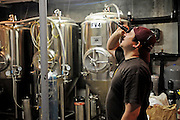 Drew Huerter, head brewer at the Mattingly Brewing Co., checks the gravity on a batch of Black Sky Stout Porter.