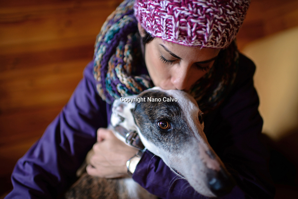 Young woman hugging her greyhound dog