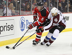 Oct 15; Newark, NJ, USA; New Jersey Devils defenseman Colin White (5) and Colorado Avalanche goalie Peter Budaj (31) fight for the loose puck during the first period at the Prudential Center.