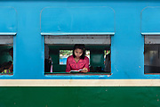 A young woman, framed in a  railway carriage window, is reading a book before her train departs.
