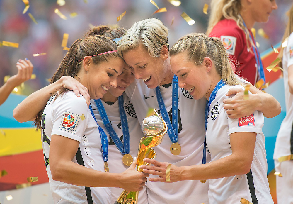 Alex Morgan (left), Lauren Holiday, Abby Wambach, and Whitney Engen of team USA celebrate with the World Cup trophy after their victory during 2015 women's World Cup Soccer in Vancouver during the final between USA and Japan.