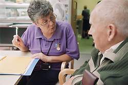 Female staff nurse talking to elderly man while she makes assessment on his progress,