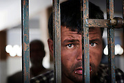 A young mentally ill man  peers through the bars of his room at the Edhi Foundation Home for Men and Boys on the outskirts of Karachi. The facility currently holds some 1132 men and 300 boys with a staff of 40 including one doctor. Te shelter acts as a 'catch all' safety net giving those who are mentally or physically disabled as well as those who have no where else to go a refuge in a the absence of any state help. most at the facility have been abandoned by their families, and have nothing in the way of personal possessions, the clothes they wear are mostly donated. there are no education/voactional training facilities on site for adults and medical support is basic at best...The youngest, a mentally disable boy is 8 years old whilst the oldest, an 84 years old homeless person. According to Dr Kamal the resident doctor, there are about 80-100 admissions in a week to the senior citizens hall while between approximately 16 people die every month, mostly because of old age. ..The mentally disabled patients receive occasional consultant visits and whilst they are administered prescribed medicines to keep them manageable, no measures are taken to improve their condition or help them become independent in their daily routine...The Edhi facility is able to meet merely their survival needs of the men and boys. Some patients are visited by relatives, very few leave the facility unless there is a guarantee of care from a relative. meals are basic consisting of traditional biryani type rice dish and there is little in the way of running water and electricity. At the time of visit water bowsers were being delivered to the the facility to cater for water consumption. patients sleep some 30 to a room some as may as 80 depending on the mental and physical abilities of the patients....In a country of some 160 million people, affordable medicines and diagnostic tests are beyond the reach of most people in Pakistan. The country suffers from shortage of doctors and government funded