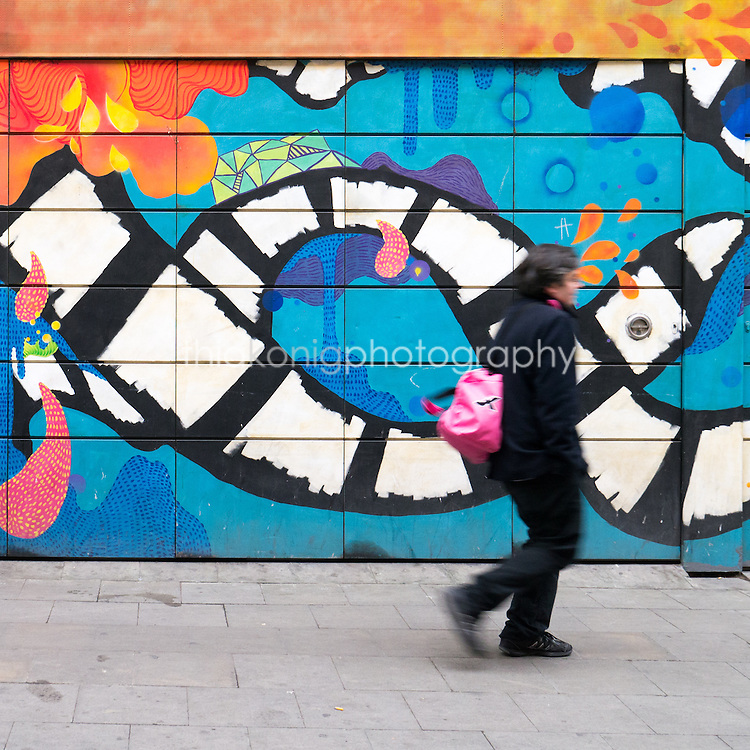 A woman walks in front of a colorful wall mural, Barcelona, Spain.