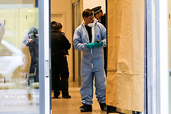 © Licensed to London News Pictures. 23/11/2019. London, UK. A forensic officer and police officers are seen inside Blakeney Tower on Buckle Street in Tower Hamlets, East London following a fatal stabbing.<br /> Police were called to a residential address in Blakeney Tower on Buckle Street, Tower Hamlets in East London at 08.48hrs this morning following reports of a stabbing. A male, in his 20s, was found with stab injuries. Despite the efforts of emergency services, he was pronounced dead at the scene. Three other males with stab injuries were treated at the scene by paramedics before being taken to hospital. Photo credit: Dinendra Haria/LNP