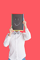 Man holding smiley face sign over red background