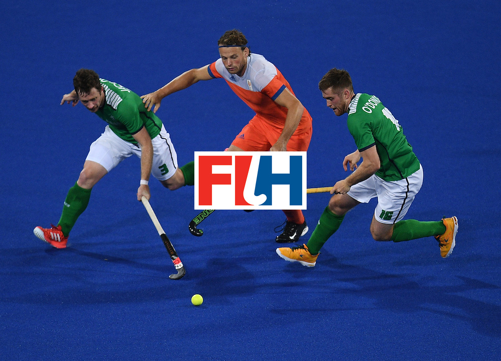 Netherland's Seve van Ass (C) chases the ball with Ireland's John Jackson (L) and Shane O'Donoghue during the men's field hockey Netherlands vs Ireland match of the Rio 2016 Olympics Games at the Olympic Hockey Centre in Rio de Janeiro on August, 7 2016. / AFP / MANAN VATSYAYANA        (Photo credit should read MANAN VATSYAYANA/AFP/Getty Images)