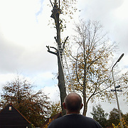 Stormschade Hinde Huizen, boom op huis, brandweer zagen