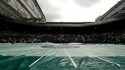 Ground staff put the covers on centre court as rain stops play on day three of the Wimbledon Championships at the All England Lawn Tennis and Croquet Club, Wimbledon.