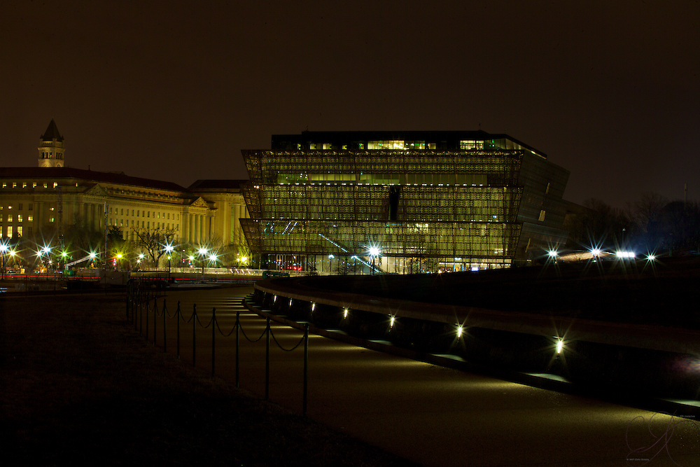 The stunning exterior of the National Museum of African American History and Culture at night as seen from the Washington Monument.