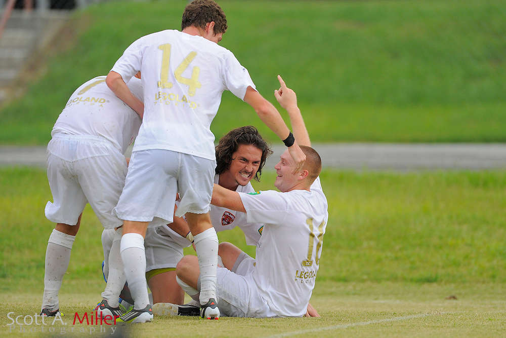 Orlando City midfielder Sam Fairhurst (16) celebrates with forward Drew Helm (23), midfielder Gonzalo de Mujica (14) and midfielder Nicolas Russo (7) after scoring during their 4-2 win over the Austin Aztex in PDL Southern Conference Championships final at Trinity Catholic High Schooll on July 22, 2012 in Ocala, Florida. ..©2012 Scott A. Miller