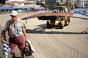 "Tenerife / Los Cristianos June 7, 2006 - Tourist in front of wrecked fishing boat of refugees on the beach - A fishing boat called ""Cayucos"" by the inhabitants of the island, with 85 would-be immigrants from West Africa intercepted by Spanish police of the coast of Tenerife in the Canary Islands are seen in an open wooden fishing vessel as they approach the port of Los Cristianos. They arrived on June, carrying 85 would-be immigrants, in the archipelago which has received more than 7,000 Africans so far this year, more than half to the tourist resort island of Tenerife. At least 1,000 more are believed to have died trying to make the sea crossing, mostly in small fishing boats"