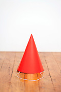 a red paper party hat on a wooden floor against a white wall