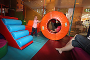 Indoor children's playground child rolls in a tube