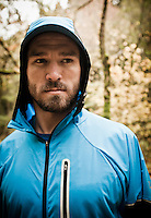 Portrait of a bearded young man wearing a hooded running jacket.