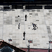 April 6, Porto, Portgual : Young boys, backlit by the sun, cast long shadows as they play soccer in a square in downtown Porto. CREDIT: Karsten Moran / Redux Pictures