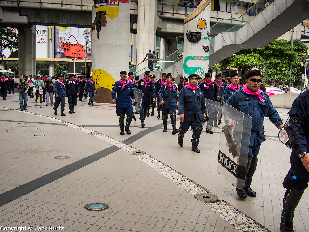 """14 JULY 2013 - BANGKOK, THAILAND:  Thai riot police head walk across the plaza in front of the Bangkok Arts and Culture Centre after about 150 members of the so called """"White Mask"""" movement marched through the central shopping district of Bangkok Sunday to call for the resignation of Yingluck Shinawatra, the Prime Minister of Thailand. The White Mask protesters are strong supporters of the Thai monarchy. They claim that Yingluck is acting as a puppet for her brother, former Prime Minister Thaksin Shinawatra, who was deposed by a military coup in 2006 and now lives in exile in Dubai.       PHOTO BY JACK KURTZ"""