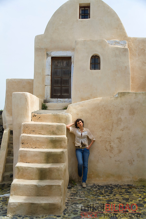 woman and old house.<br /> Santorini island, Cyclades islands, Aegean Sea, Greece, Europe