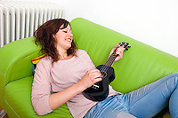 Young woman lying on couch playing ukulele