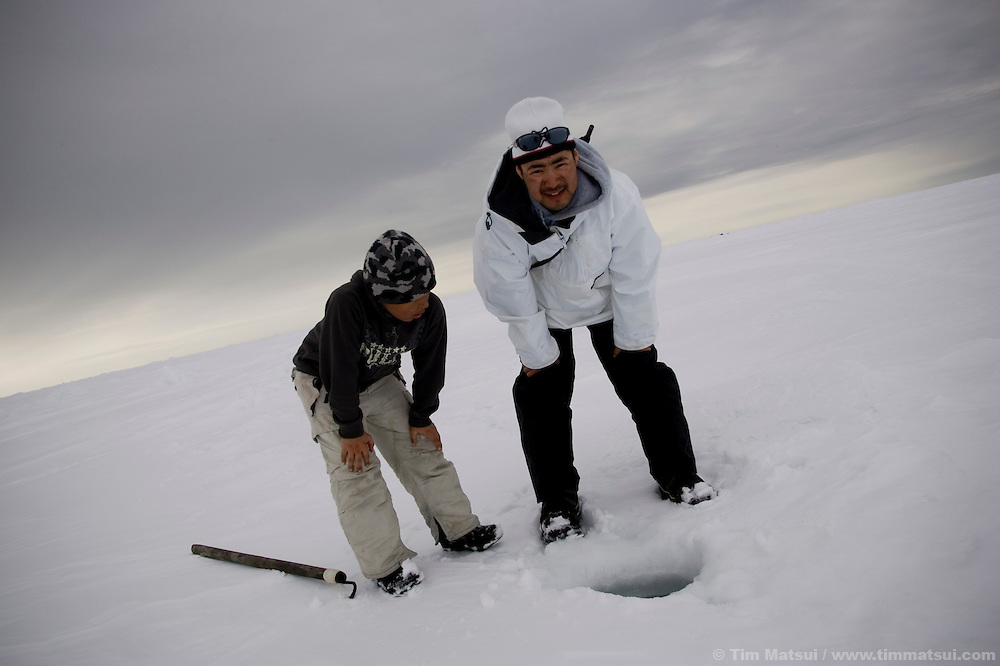 May 3, 2008 -- Kivalina, AK, U.S.A..Luke Koonook III and nine year-old Justin Cooper Swan stalk a seal at its breathing hole on the pack ice, some two miles from shore and 12 miles from the native village of Kivalina, Alaska. Kivalina is suing 20 oil companies for property damage related to global warming; the ocean pack ice forms later and melts earlier, leaving the town vulnerable to erosive winter storms and endangering their traditional subsistence lifestyle. (Photo by Tim Matsui)