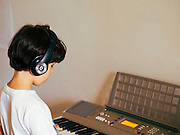 young boy of seven produces music on a Synthesizer keyboard
