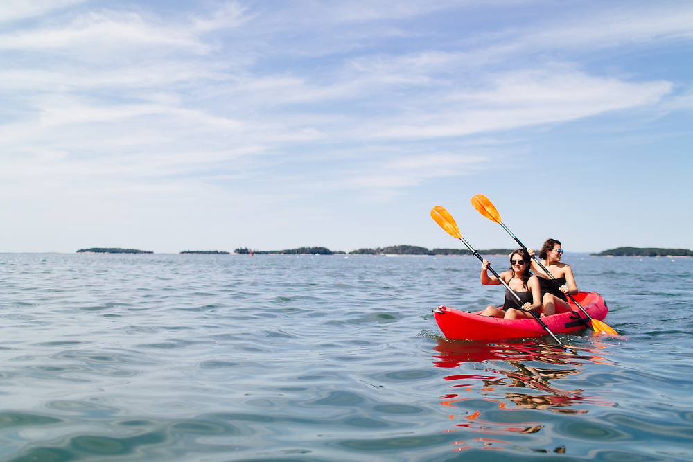 Young Women Kayaking on Ocean, Vinalhaven, Maine.