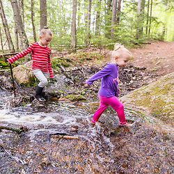 Two young girls play in the woods at the Orris Falls Preserve in South Berwick, Maine.