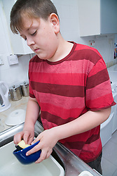 Young boy who is a carer for his mum; who is severely asthmatic; washing up,