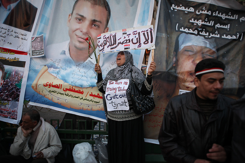 A woman chants beside posters of some of the more than 300 people killed by Mubarak's forces during protests calling for his ouster.