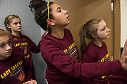 Members of the Federal Hocking Lady Lancers 8th grade girls basketball team peer onto the court from the locker room before their first tournament game at Wellstone Middle School in Waverly, Ohio. The team finished their season undefeated 17-0.