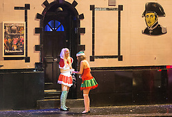 "© Licensed to London News Pictures . 20/12/2014 . Manchester , UK . Two women dressed in seasonal costumes outside Napoleons pub on Bloom Street . "" Mad Friday "" revellers out in the rain and cold in Manchester . Mad Friday is typically the busiest day of the year for emergency services , taking place on the last Friday before Christmas when office Christmas parties and Christmas revellers enjoy a night out .  Photo credit : Joel Goodman/LNP"