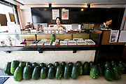 Kougan winter melons used to make traditional sweets are lined up by the counter as staffer Haruka Ishimine arranges some products at the Janaha Kippan-ten store in Naha, Okinawa, Japan on 27 June 2012. Today the Jahana family are the only people still making the traditional Kippan and Tougan sweets that were served at the court of the Ryukyu kings over 300 years ago. Photo: Robert Gilhooly.