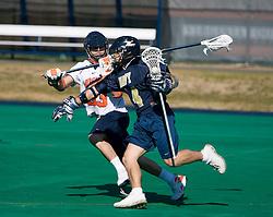 Navy attackman Tim Paul (14) runs past Virginia defenseman Matt Kelly (33).  The Virginia Cavaliers scrimmaged the Navy Midshipmen in lacrosse at the University Hall Turf Field  in Charlottesville, VA on February 2, 2008.