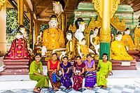 YANGON, MYANMAR - DECEMBER 16, 2016 : women posing in front Buddha statues of the Shwedagon Pagoda at Yangon (Rangoon) in Myanmar (Burma)