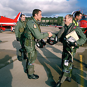 Sqn. Ldr. Spike Jepson leader of the 'Red Arrows', Britain's Royal Air Force aerobatic team congratulates his pilots. ..Today they have reached the all-important milestone of 'first 9-ship' (when all nine aircraft have flown a basic air show display together, after two groups have practiced separately) and is the culmination of five months rigorous Winter training. They stand proud with beaming smiles on a warm spring day, their flying helmets with those famous arrows pointing towards blue sky and fluffy clouds. Still dressed in green flying suits, they go on to their spring training ground at Akrotiri, Cyprus where they earn the right to wear red suits, known around the world.