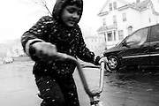 SYRACUSE, NY – NOVEMBER 27, 2010: Ram Khatiwoda, 11, rides his bicycle in the first snowfall in Syracuse's North Side. As a Nepali refugee, Khatiwoda moved into the area with his family three months earlier.