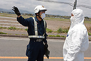 Government officials in contamination suits talk with a policeman at a police roadblock set up on Route 6 in Minami Soma reinforce the 20 kilometre exclusion zone around Fukushima Daiich nuclear power station which was damaged in the march 11th earthquake and tsunami causing radiation leaks and explosions. Minami Soma, Fukushima, Japan. Wednesday May 4th 2011