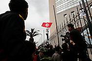 TUNISI. UN MANIFESTANTE SVENTOLA LA BANDIERA DELLA TUNISIA AGGRAPPATO AI CANCELLI DEL PALAZZO DELLA SEDE DEL PARTITO RCD DELL'EX PRESIDENTE TUNISINO BEN ALI;