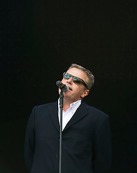"""© Licensed to London News Pictures. 27/08/2011. Reading, UK. Madness play the main stage on day two of Reading Festival 2011 in Reading, Berkshire today (27/08/2011). Pictured is lead singer Graham """"Suggs"""" McPherson Photo credit: Ben Cawthra/LNP"""
