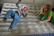 Brodee Davis, 3, shoots in the air after his sister Melanie Otten, 9, flops down on an air mattress in her bedroom on their first day in a new apartment in Claremont, N.H. Thursday, June 4, 2015. Davis and Otten had been living with their parents Marsha Barger Alexander and Elijah Alexander in Claremont's homeless shelter and the family was given housewares and clothing by Baby Steps on their move-in day. (Valley News - James M. Patterson)<br /> Copyright &copy; Valley News. May not be reprinted or used online without permission. Send requests to permission@vnews.com.