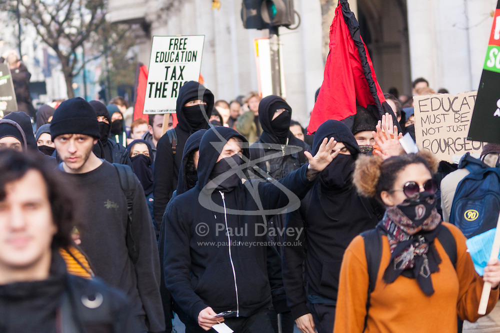 London, November 19th 2014. Thousands of students march through central London, demanding that education fees are scrapped by the government. PICTURED: Masked anarchists march with the students.