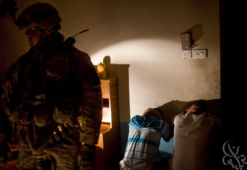 U.S. Army 1-23 Stryker soldiers search Iraqi men by flashlight during an early morning raid June 19, 2007 in Bacouba, Iraq. U.S. and Iraqi forces have begun a new sweep of Bacouba and other locations across central Iraq  intended to root out Al Qaeda fighters across what officials call the outer Baghdad belt. ..
