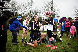 © Licensed to London News Pictures. 03/03/2019. Dorking, UK. Winners of the race CHRIS HEPWORTH proposes to his partner TANISHA PRINCE at the finish line. Competitors take part in the 2019 annual Wife Carrying Race in Dorking, Surrey. Run over a course of 380m, with both men and women carry a 'wife' over obstacles, the race is believed to have originated in the UK over twelve centuries ago when Viking raiders rampaged into the northeast coast of England carrying off any unwilling local women . Photo credit: Ben Cawthra/LNP