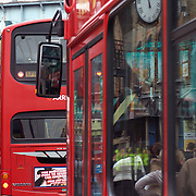 Crowds of people on sidewalk reflected in glass window of red doubledecker London bus, Camden High Street, Camden Market, Camden Town, London, England, UK<br />