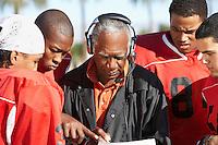 Football players surrounding coach on field