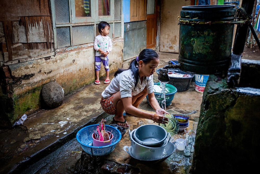 A local resident of Cilawengke village wash dishes with water contaminated by toxic wastes. Residents could only afford to purchased water for drinking and cooking...Credit: Andri Tambunan for Greenpeace