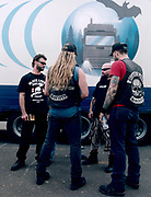 Four bikers standing together and talking in front of a trailer.