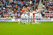 Leeds United player huddle before kick-off during the EFL Sky Bet Championship match between Wigan Athletic and Leeds United at the DW Stadium, Wigan, England on 17 August 2019.