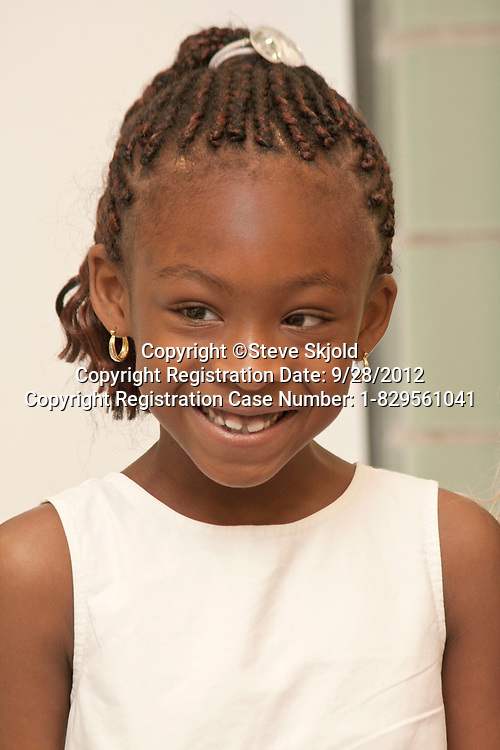 Happy Black African American first grade female student in the classroom. Horace Mann School St Paul Minnesota MN USA